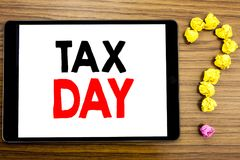 Writing text showing Tax Day. Business concept for Income taxation Refund written on tablet computer on the wooden background with. Writing text showing Tax Day royalty free stock image