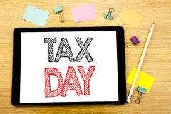 Writing text showing Tax Day. Business concept for Income taxation Refund Written on tablet laptop, wooden background with sticky. Writing text showing Tax Day stock photography