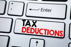 Writing text showing Tax Deductions. Business concept for Finance Incoming Tax Money Deduction written on white keyboard key with. Copy space. Top view stock photo