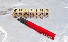 Writing. Text ' Writing ' in upper case letters on small white cubes together with red fountain pen on silver reflecting background Stock Image