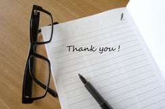 Writing A Thank You Note. A thank you car with glasses on a wooden desk Writing a Thank You Note Stock Photos