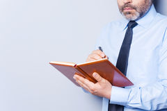 Writing a To-Do list. Confident mature man in shirt and tie writing something in note pad while standing against grey background royalty free stock image