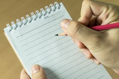 Writing to do list with red pencil and notebook. Hand holding red pencil and notebook writing to do list, close up top view Royalty Free Stock Images