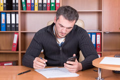 Writing unshaven man in office Stock Photo