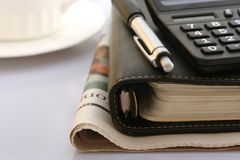 Writing Utensils. Calculator,ballpoint,notebook,newspaper and coffee cup Stock Image