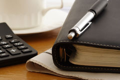 Writing Utensils. Calculator,ballpoint,notebook,newspaper and coffee cup Royalty Free Stock Photography