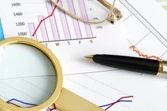 Writing Utensils on Financal Documents. Magnifying glass, pen and glasses on financal documents Stock Photo
