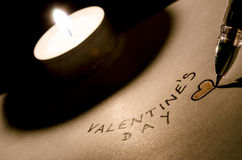 Writing a valentine text by the candle Royalty Free Stock Image