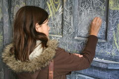 Writing on the Wall. Young girl writing on a wall in New York City Stock Image
