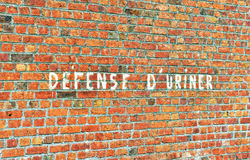 Writing on the wall. In French calling to keep the environment clean and do not piss on the street Stock Images