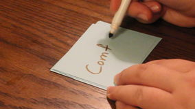 Writing weak. Young women`s hand writing the word weak on a white card stock footage