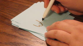 Writing weak. Young women`s hand writing the word weak on a white card stock video footage