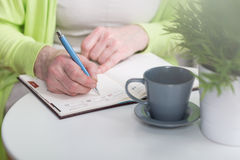 Writing in weekly organiser. Close-up of woman writing in weekly organiser Stock Images