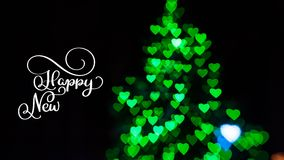 Writing white Happy New Year animation calligraphy lettering text on dark with green bokhe background. Christmas 3D For stock video