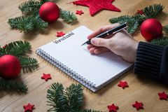 Writing a wish list for Christmas in German on a notepad with Ch Stock Images