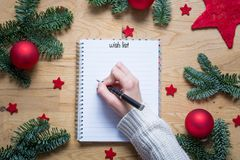 Writing a wish list for Christmas on a notepad with Christmas de Royalty Free Stock Photo