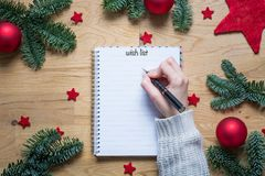 Writing a wish list for Christmas on a notepad with Christmas de Stock Photography