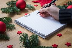 Writing a wish list for Christmas on a notepad with Christmas de Royalty Free Stock Photos