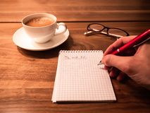 Writing a wish list with a pen on a notepad for xmas royalty free stock image