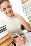Writing woman with textbooks royalty free stock photo
