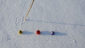 Writing word December on snow and Christmas balls stock video footage