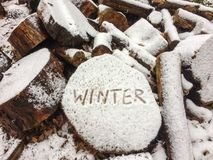 Writing of the word winter on a block of wood after first snow.  stock photos