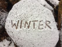 Writing of the word winter on a block of wood after first snow, close-up.  royalty free stock photography
