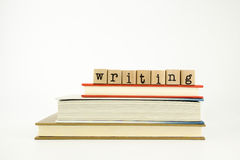 Writing word on wood stamps and books Royalty Free Stock Photography