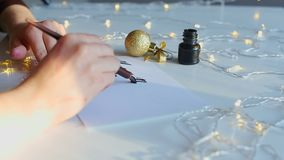 Writing words with black ink. Calligraphy inscription with broad nib pen and black ink. Decorated space with shimmering yellow LED lamps and fir tree toy stock video footage