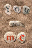 Writing words on the stones in black and red ink. Words written on the stones with sand in the background Royalty Free Stock Images
