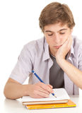 Writing young male student with books Stock Photo