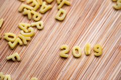 2019 written with alphabet pastas on wood background royalty free stock photos