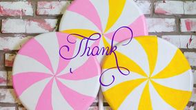 Written animation Thank you calligraphy lettering text with Ornate frame elements on pink and yellow candys background. Filigree divider animation words stock video
