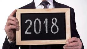 2018 written on blackboard in businessman hands, annual report, motivation stock photo