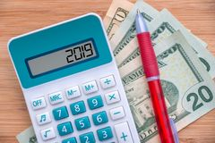 2019 written on a calculator and dollars banknotes on wood background stock image