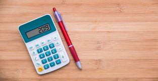 2019 written on a calculator and a pen on wood background. 2019 written on a calculator and a pen on wooden background royalty free stock photos