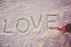 Written or drawn by hand in pink glove word LOVE on white snow Royalty Free Stock Photo