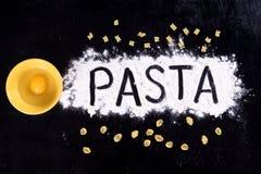 On written flour pasta. Broken egg. Spilling pasta. Top view stock image