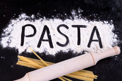 On written flour pasta. Dark background. Rolling pin lies on macaroni Royalty Free Stock Photography