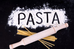 On written flour pasta. Dark background. Rolling pin lies on macaroni. Top view Stock Photography