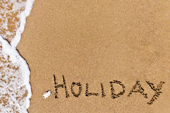 Written holiday drawn on the sand. On a beach Stock Photo
