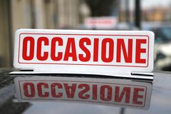 Written Italian saying OPPORTUNITY over the used car Stock Image
