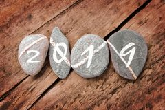 2019 written on a lign of stones on a wood background. 2019 written on a lign of stones on a wooden background stock images