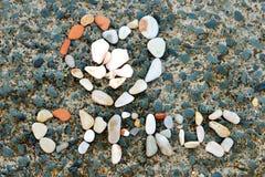 Written pattern of sea shells and stones on rock Stock Photo