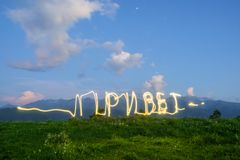written in Russian `Hello` freezelight drawing by light of a LED flashlight in the air with mountains royalty free stock images