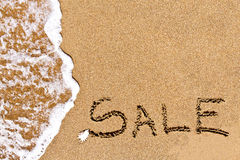 Written sale drawn on the sand Stock Image