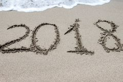 2018 written on the sand of a beach, closeup royalty free stock images
