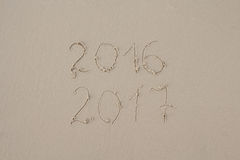 2016 and 2017 written on sand at the beach Royalty Free Stock Photo