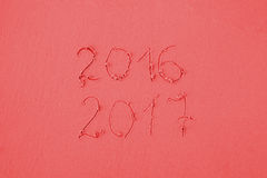 2016 and 2017 written on sand at the beach in red colors Stock Image