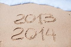 2012 and 2013 written in sand on beach Royalty Free Stock Images